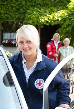 Pflegerin vor ASD-Fahrzeug