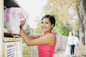 Junge Frau wirft Kleiderspende in Container