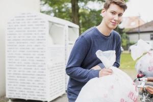Junger Mann mit Kleidersäcken
