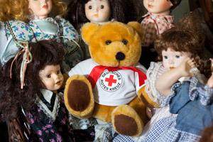 Puppen und ein Teddybär mit einem Logo-T-Shirt