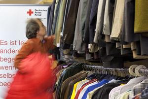 Kunde mit roter Jacke über dem Arm schaut sich Anzugsjacken an