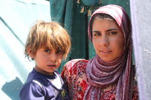 Flüchtlingskind auf dem Arm der Mutter in die Kamera schauend