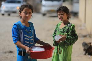 Flüchtlingsmädchen mit Eisblöcken in einer Schüssel