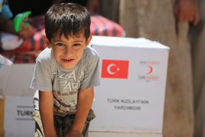 Flüchtlingsjunge vor Hilfsmittelpaket des Türkischen Roten Halbmondes