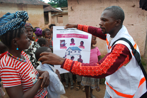 Ebola - Ein Freiwilliger Helfer erklärt in einem Dorf in Guinea die Verbreitungswege des Virus